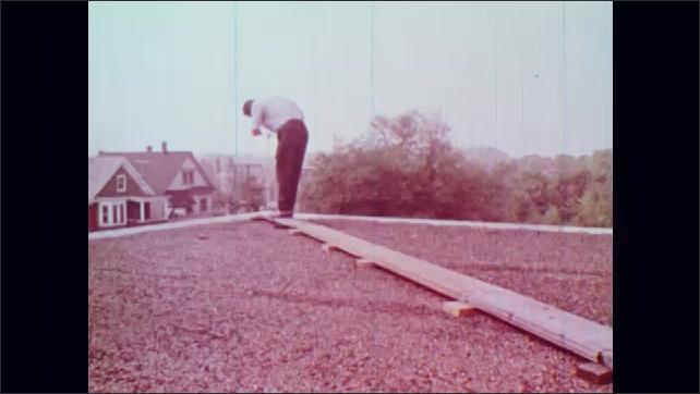 1970s: Hazy cityscape. Man walks across board. Man places slide under microscope.