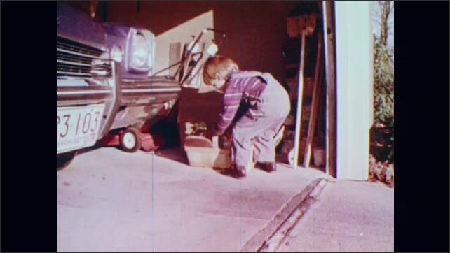 1970s: UNITED STATES: child picks up bulbs from basket. Girl shows bulb to camera. Boy plays with seeds in garage. Seeds on floor.