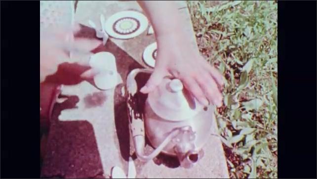 1970s: UNITED STATES: hand puts leaves in pot. Children pretend to make tea in garden