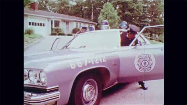 1970s: UNITED STATES: lady carries child from home. Police car outside home. Patrol car drives along street.
