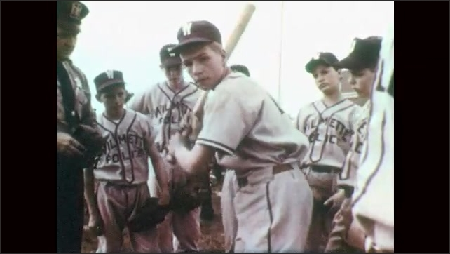 1950s: UNITED STATES: Division of Crime Prevention workers. Police organise baseball match with students. Man assigns paperwork to officers. Boy with baseball bat