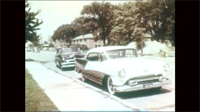 1950s: UNITED STATES: cars drive along road. Police car pulls over vehicle on street. Light on roof of car. Officer speaks to driver of car