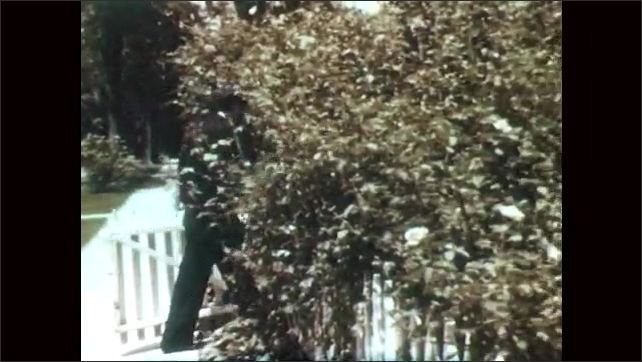 1950s: UNITED STATES: policeman meet father from work. Policeman arrives home to family. Man walks to house with children