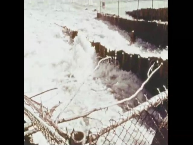 1970s: Piles of bags of fertilizer. Water pours out of industrial pipe into lake. Green algae in water.