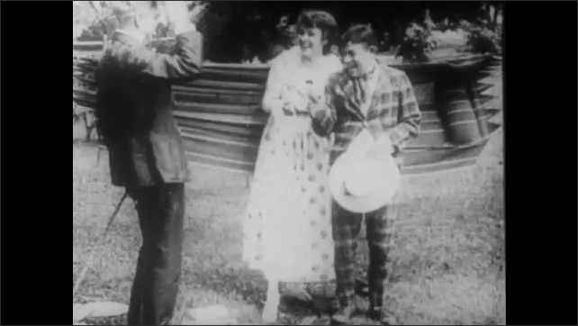 1910s: A man pulls a needle out of the rear end of his plaid suit. He and woman turn to look at something stuck to the rear end of another man's pants. The men fall as they try to sit on a hammock.