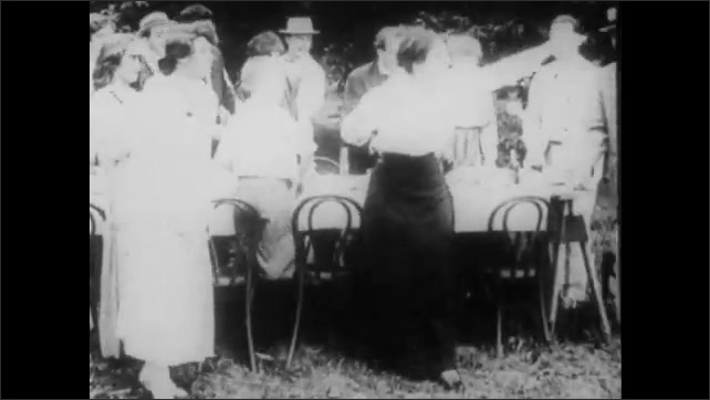 """1910s: Two men sit in the grass, arguing. Intertitle reads, """"At the picnic."""" A crowd surrounds a table. Two women point and the crowd laughs at the men. One man hits the other with a cane."""