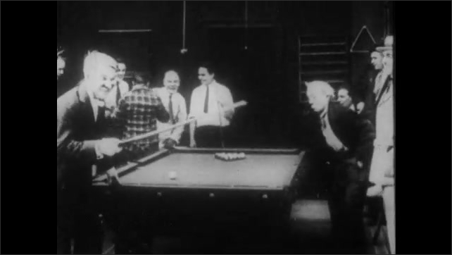1910s: A cue ball hits a man in the eye. A man hits him with a pool cue as a crowd gathers. He takes another shot. The balls go in the holes, then return to their original formation.