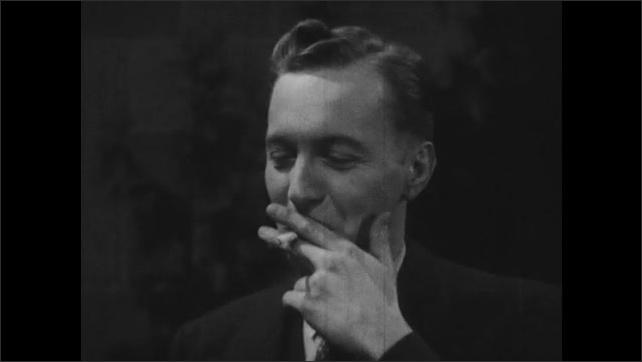 1940s: Man laughs and talks. Man smokes.