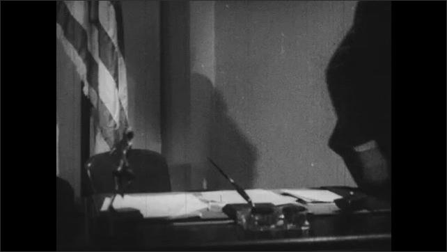 1940s: Man sits at desk and writes. Men walk through doorway. Men speak while standing. Men shake hands.