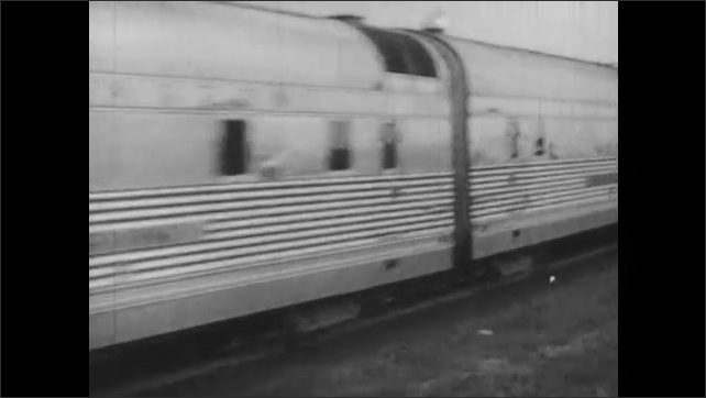 1940s: Helicopter flies through the air. Train on train track. Man talks. Teacher and students work in classroom.