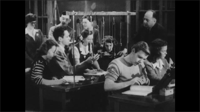 1940s: Students work in group. Students in physics lab. Teacher speaks.