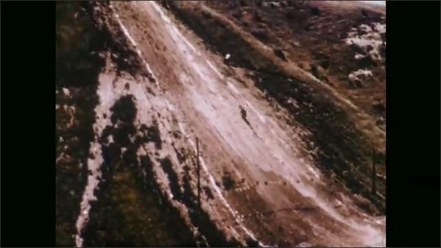 1970s: UNITED STATES: Man rides bike up steep slope. Man comes off bike.