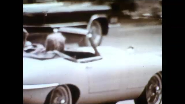1960s: Man and woman drive in sports car. Man and woman pose by car with map. Man and woman pose with open car hood. Pigeons fly from ground. Woman poses at water fountain.