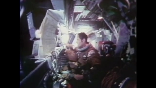 1980s: Astronaut sits in cockpit of space shuttle with helmet in bag. He ties bag with helmet to dashboard where it floats in zero gravity.