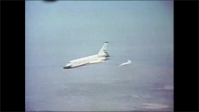 1980s: UNITED STATES: space shuttle flies in sky. Shuttle flies over Earth. Parachute behind shuttle