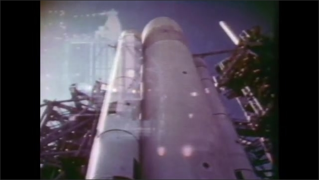 1980s: UNITED STATES: space craft on launch pad. Engineers work on space craft. Gantry at night.