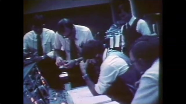 1980s: UNITED STATES: NASA crew at headquarters. Man with equipment. Launch day at NASA base command. Space craft on gantry