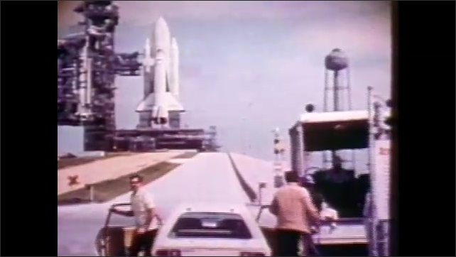 1980s: UNITED STATES: Stop sign by vehicle. Space craft on gantry before launch. Car parks near space ship
