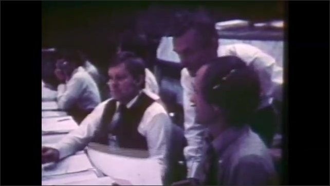 1980s: Crowd of spectators sit.  Pilots talk on runway.  Men work in mission control room.