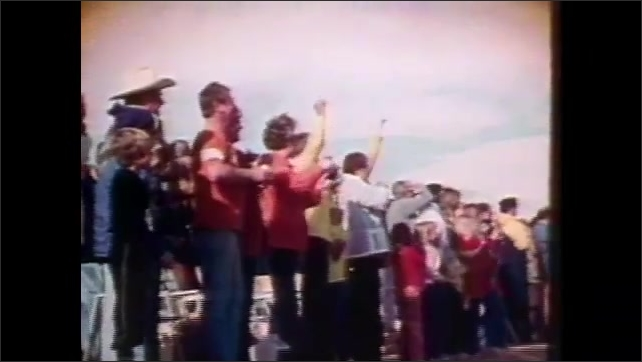1980s: People watch sky and cheer.  Man takes picture.  Space shuttle in air.