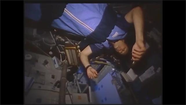 1990s: Astronauts sleep on board space shuttle. Astronaut loads cartridge into camera.