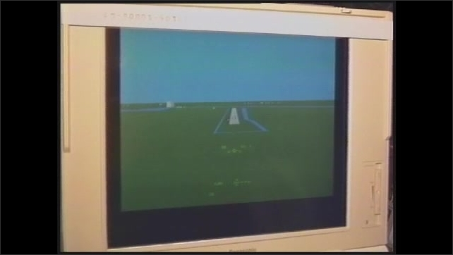 1990s: Laptop computer screen. Astronauts sits in front of computer on board the space shuttle.