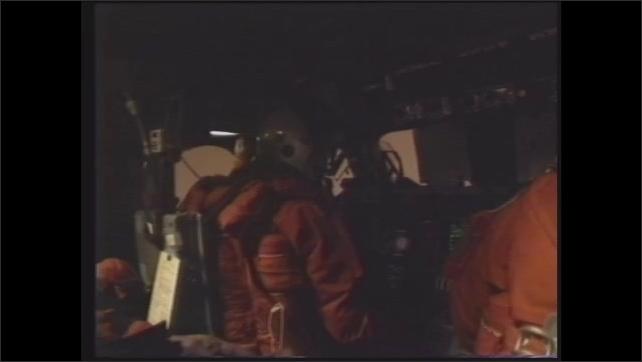 1990s: Astronauts sit in cockpit of space shuttle. Window of space shuttle.