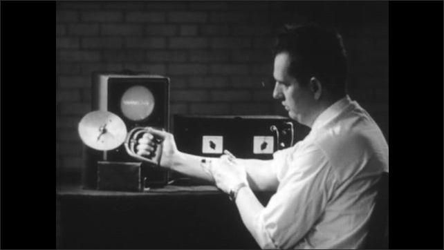 1940s: Man's arm is wired to a machine and he flexes his arm. Close-up of monitoring equipment taped to his inside arm.
