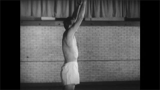 1940s: Shirtless man in shorts throws a basketball underhand. Shirtless man in shorts does several handsprings in a row and then walks on his hands. Man does back springs on the mat.