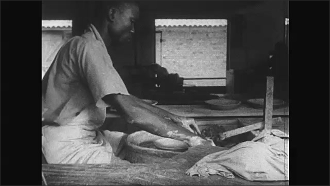 Africa 1940s: Man using potter's inspects his work. Potter uses wire to remove new-shaped plate from potter's wheel, sets plate on side table. Man at work on potter's wheel.