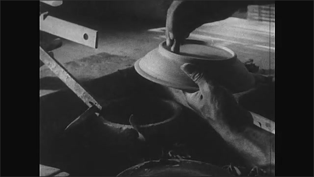 Africa 1940s: Man removes clay plate from potter's wheel, stamps underside, runs hands around rim of plate. Man throws ball of clay onto potter's wheel.