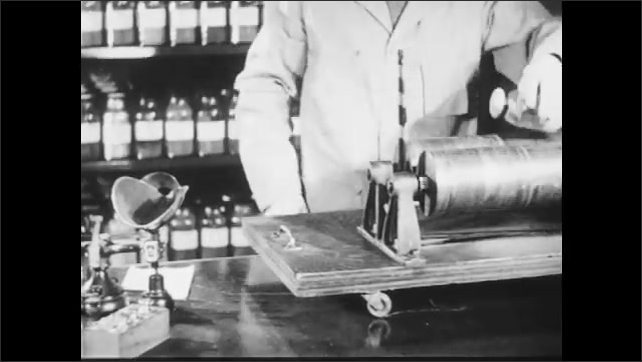 1940s: A person puts powder into a jar in a lab, the person closes the jar tightly and puts it on a device that rotates. Jar with powder inside rotates on a device.