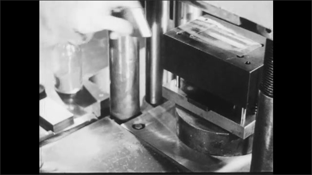 1940s: Hand clears knife, puts the knife and jar to the side, hands put the device on the machine and cover the slot with two small pieces on top of each other.