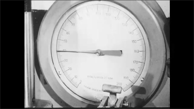 1940s: Man takes out his hands from a machine in a lab and pulls a switch that turns on the machine. The machine moves slowly and compacts the pieces. Barometer points to 40.