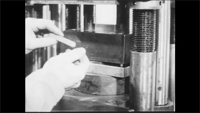 1940s: Machine moves slowly, compacts the spacers and ejects a bar from the slot, hands take the piece out from the machine and hold the bar. Fingers hold a bar made of powder metal.