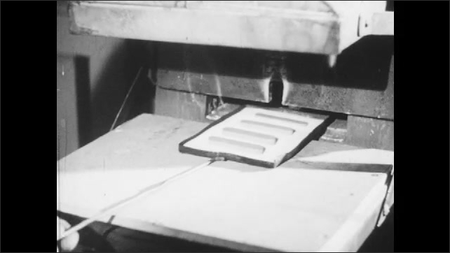 1940s: Industrial machine, worker wears mask, puts tray on machine. Hand pushes a tray with a metal stick into the furnace. The worker operates the machine, the furnace closes, he puts the stick away.