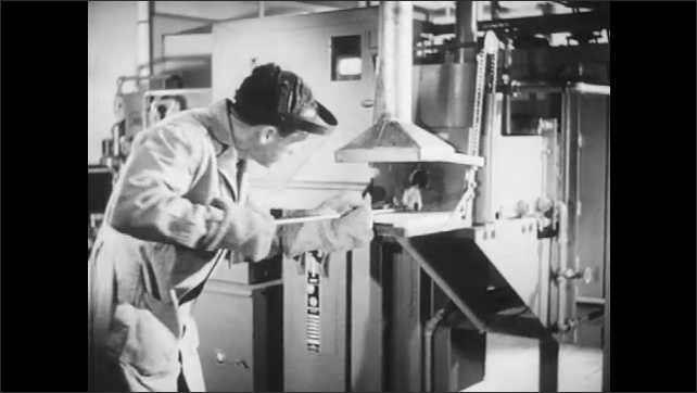 1940s: A worker wears gloves, puts a metal stick inside the furnace carefully, flames come out and he takes out the stick. Worker removes the tray from the furnace with a stick and closes the furnace.