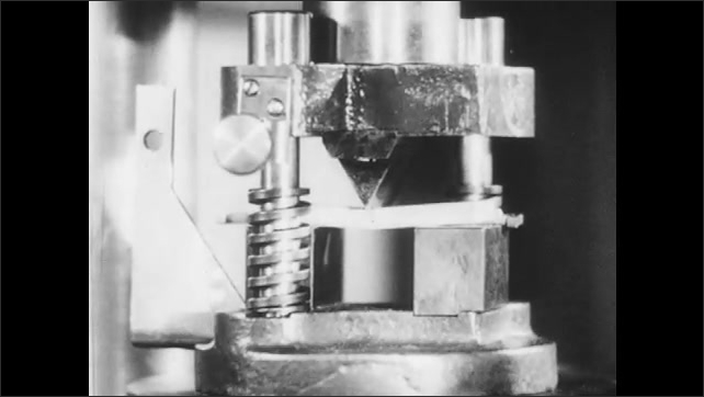1940s: Hand leans on a machine. Blocks of metal. Barometer moves up. Pressure is applied on blocks of metal. Hands remove tray from furnace with a stick, close it and hold the tray.