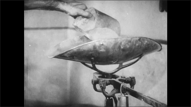 1940s: Man combines metal powders in scale bowl. Man adjusts balance scale.