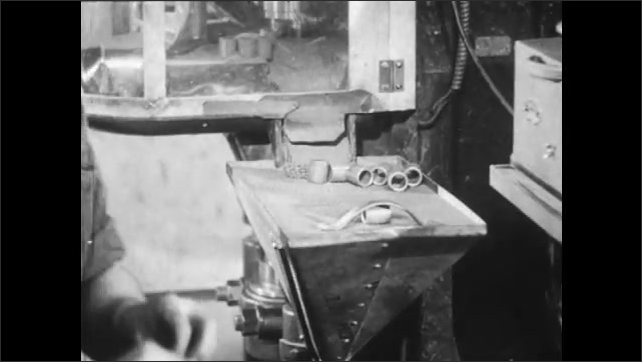 1940s: Factory worker stacks and sorts compressed metal bearings. A machine stamps out the ball-bearings and a lever pushes them along.