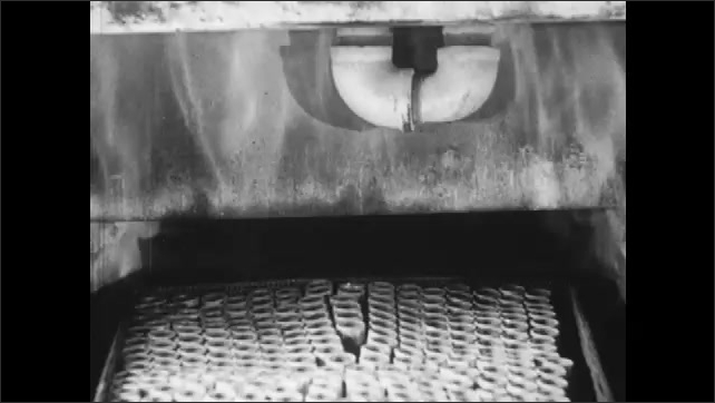 1940s: Trays of briquettes or bearing parts roll through the electric oven entrance. Flames at entrance to electric oven opening.
