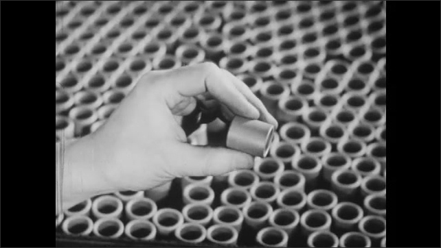 1940s: Factory worker in heat-proof gloves moves trays of briquettes or ball-bearings down a roller track from oven. Hand picks up and examines centered bearing.