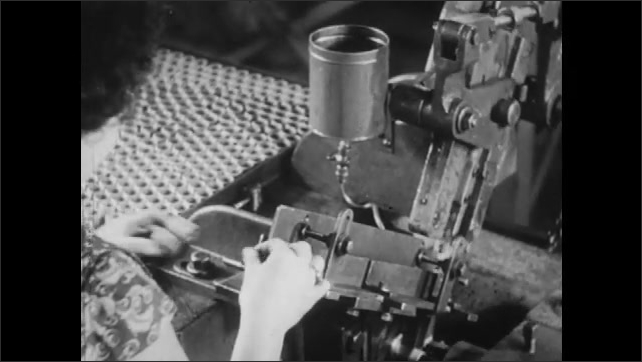 1940s: Woman factory worker removes tray of bearing from roller belt and places it in sizing machine. Worker places individual bearings or briquettes in machine die to be formed in exact shapes.