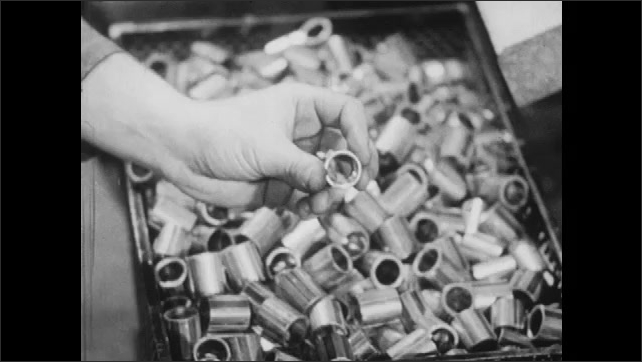 1940s: Finished metal bearings travel down to overflowing bin. Hand holds up individual bearing with burnished exterior and uniform shape.