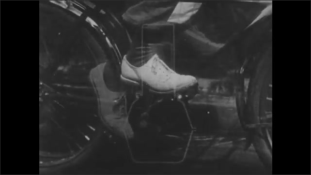 1930s: Animation of road and piston movement inside engine overlaid on man pedaling bicycle. Feet slowly pedal bicycle.