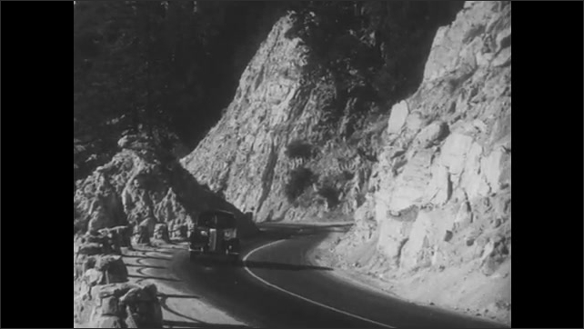 1930s: Car drives up ramp. Car drives on mountain road.
