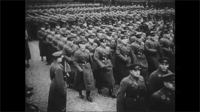 1950s: City.  Soldiers march.  Men stand.