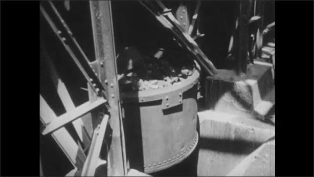 1950s: Tubing falls onto assembly line.  Machine carries vat of dirt to top of factory.  Smokestack.