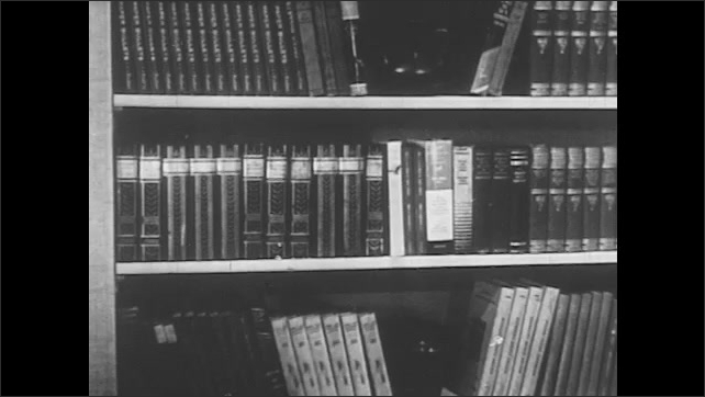 1950s: Globe rotates. Shelf full with books. Two men sit in armchairs in home library and talk.