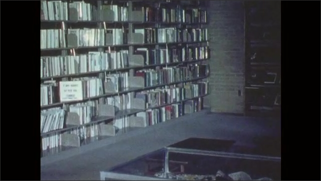 1970s: People sit in library. Shelves full of books. Sign in library